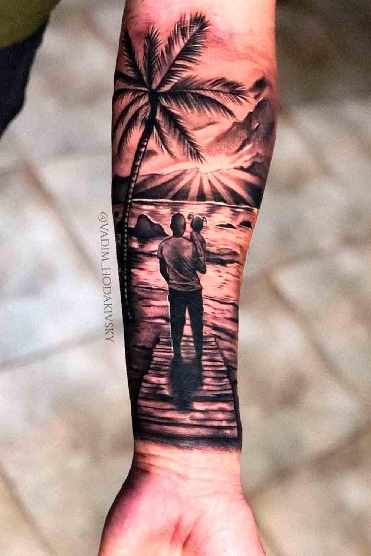 tatuagem-masculina-no-antebraco-homem-segurando-filho-na-praia
